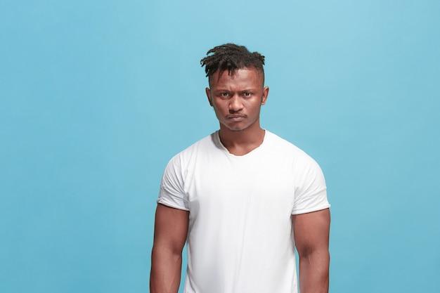 O jovem homem afro com raiva emocional sobre fundo azul studio