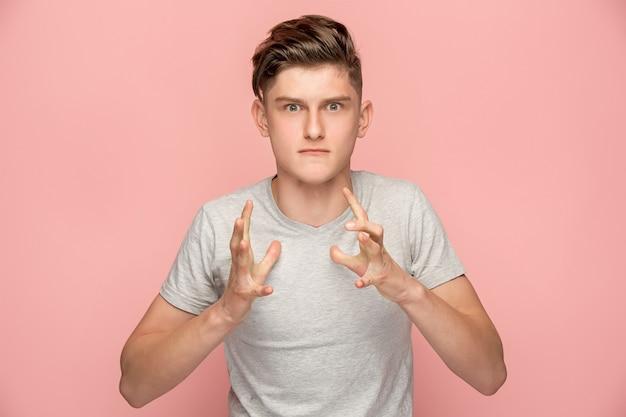 O jovem homem irritado emocional gritando no fundo rosa studio