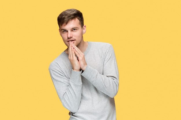 O jovem homem sério olhando com cautela e falando em segredo