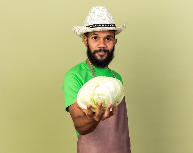 O jovem jardineiro afro-americano satisfeito com um chapéu de jardinagem e segurando um repolho para a câmera