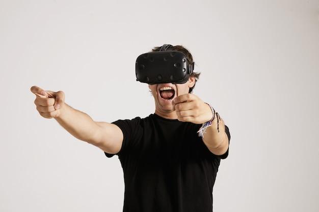 O jovem jogador emocional em um fone de ouvido de realidade virtual e camiseta preta sem etiqueta grita enquanto joga um jogo