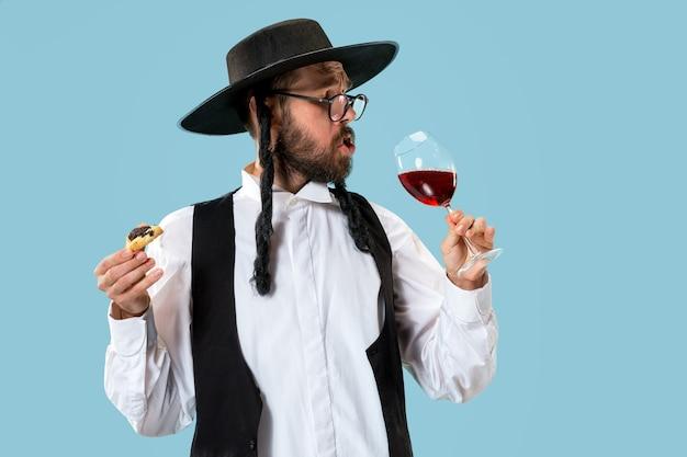 O jovem judeu ortodoxo com chapéu preto e biscoitos hamantaschen para o festival judaico de purim Foto gratuita