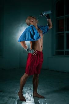 O jovem kickboxing na parede preta