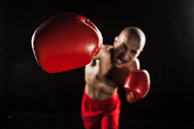 O jovem kickboxing no preto com kapa na boca