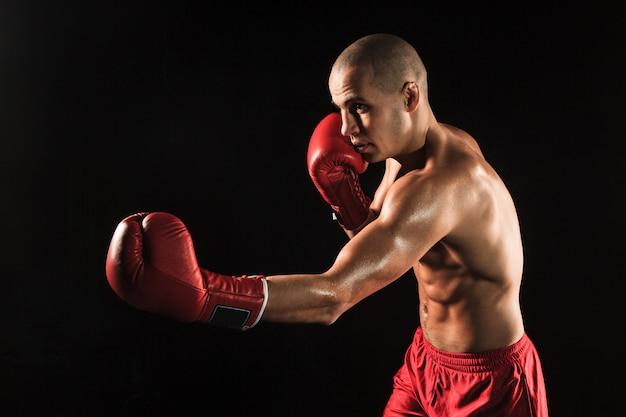O jovem kickboxing no preto