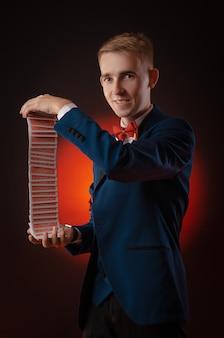 O jovem mágico está segurando cartas nas mãos
