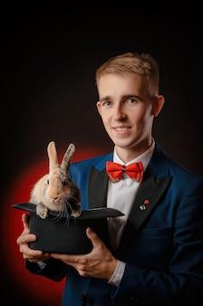 O jovem mágico ilusionista segurando um chapéu com um coelho