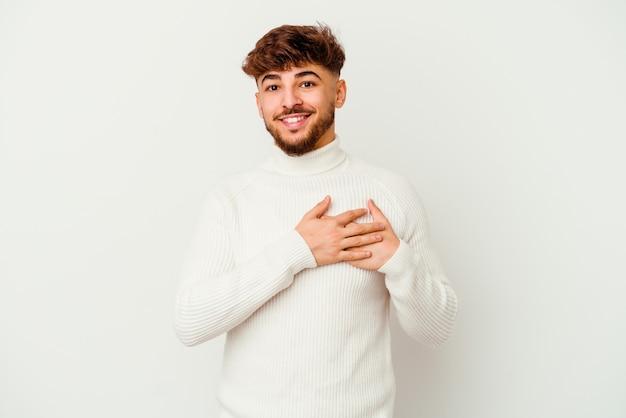 O jovem marroquino tem uma expressão amigável, pressionando a palma da mão no peito. conceito de amor.