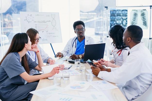 O jovem médico afro-americano mostra o resultado do paciente e fala com a equipe. grupo internacional de cinco trabalhadores médicos tem uma reunião na sala de conferências no hospital.