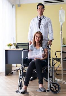O jovem médico incentivou a paciente do sexo feminino no braço quebrado e na cadeira de rodas.