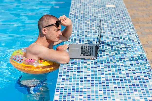 O jovem nas férias de verão com o laptop, negócios on-line. escritório em casa à distância na piscina em anel de borracha em quarentena