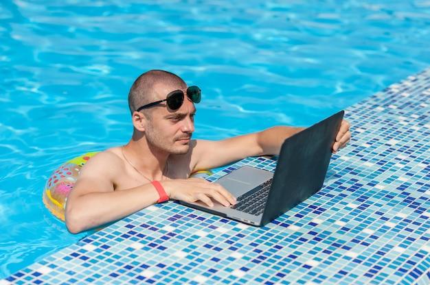 O jovem nas férias de verão com o laptop, negócios on-line. escritório em casa à distância na piscina em anel de borracha em quarentena Foto Premium