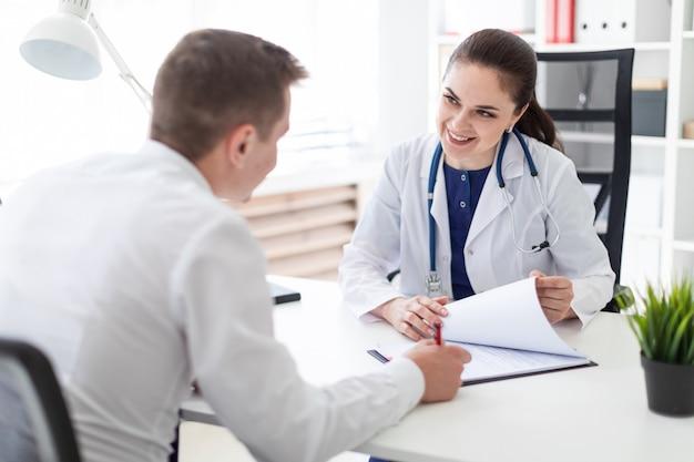 O jovem no consultório médico assina os documentos.
