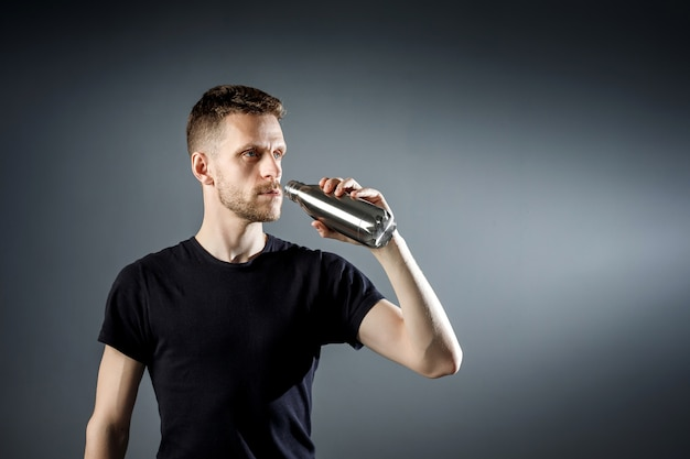 O jovem no preto está bebendo água de uma garrafa de fitness