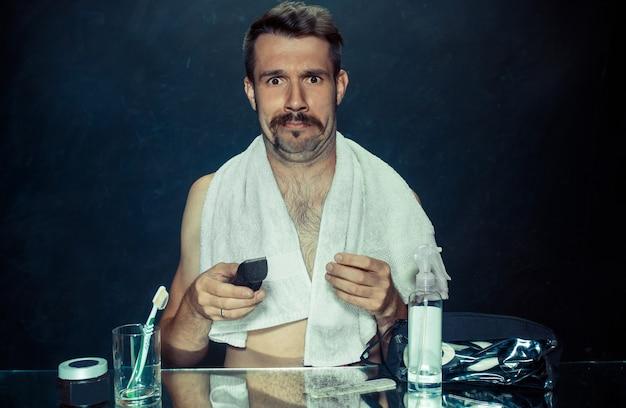O jovem no quarto sentado em frente ao espelho coçando a barba em casa. conceito de emoções humanas e problemas de pele