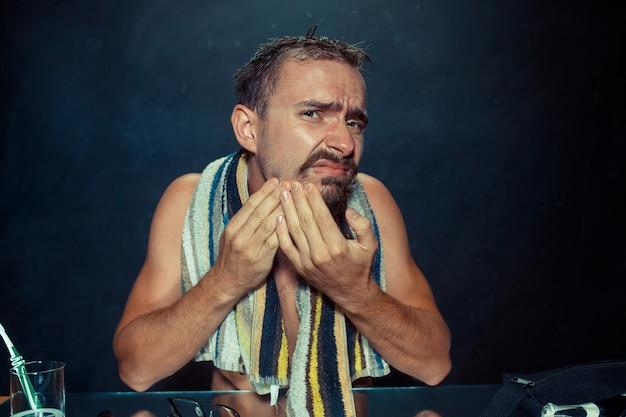 O jovem no quarto sentado em frente ao espelho coçando a barba em casa. conceito de emoções humanas