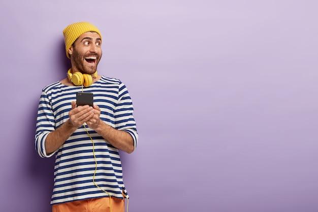 O jovem otimista feliz olha de lado, segura um telefone celular moderno, surfa na plataforma de música da internet, faz o download da música na lista de reprodução, tem fones de ouvido amarelos no pescoço