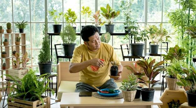 O jovem passa seu tempo livre cuidando das árvores do jardim em casa como um hobby.