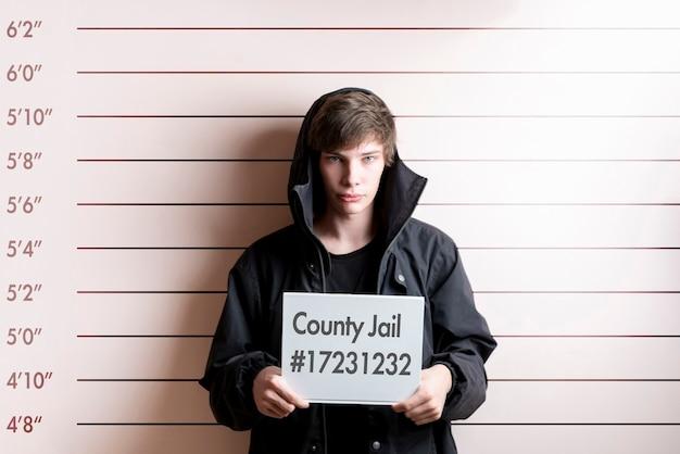 O jovem prisioneiro preso segurando um cartaz em frente ao gráfico de altura