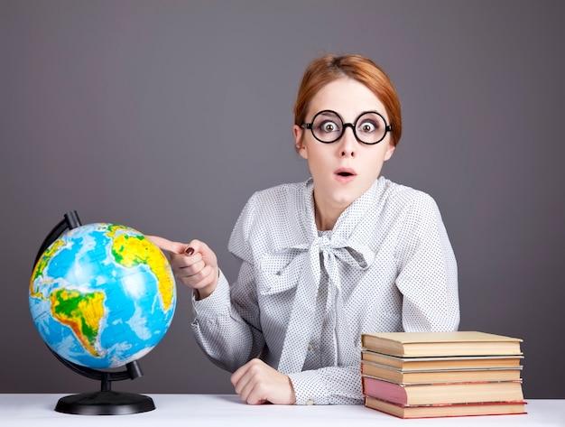 O jovem professor de óculos com livros e globo.