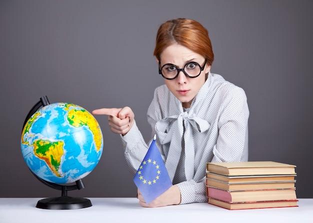 O jovem professor de óculos com livros
