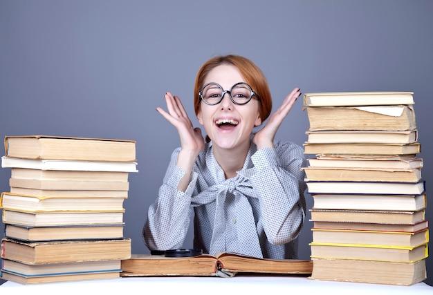 O jovem professor de óculos com livros.