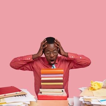 O jovem professor negro estupefato mantém as mãos na cabeça, abre a boca amplamente, olha para uma pilha de livros, prepara uma aula para os alunos