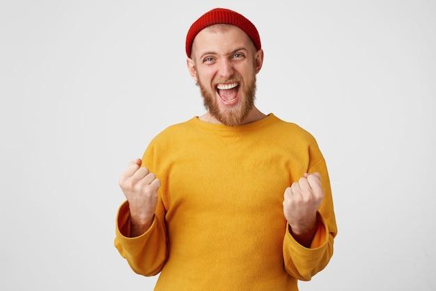 O jovem se sente um vencedor, punhos cerrados de alegria, parece incrivelmente feliz