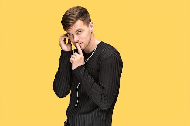 O jovem sério pedindo silêncio sobre fundo amarelo