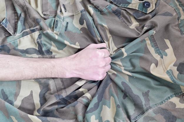 O jovem soldado agarrou o tecido do uniforme militar da segunda guerra mundial