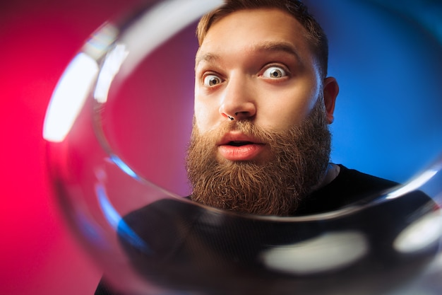 O jovem surpreso posando com um copo de vinho. rosto masculino emocional. vista do vidro. a festa, o natal, o álcool, o conceito de evento de celebração
