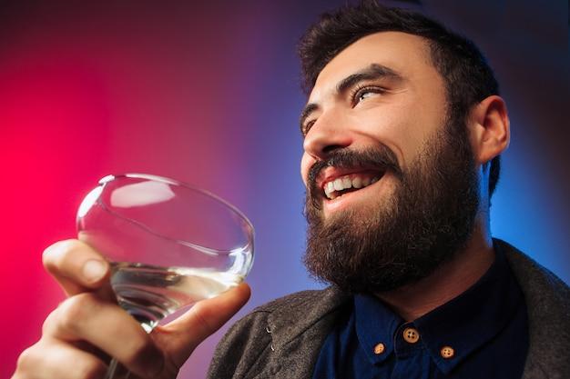 O jovem surpreso posando com um copo de vinho.