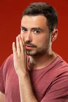 O jovem sussurrando um segredo atrás da mão sobre parede vermelha