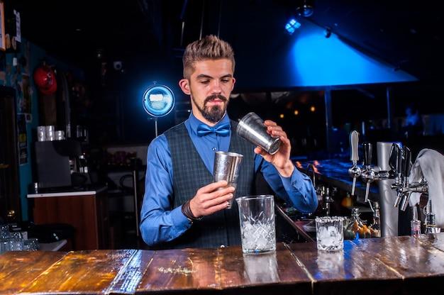 O jovem tapster surpreende com sua habilidade os visitantes do bar no balcão do bar