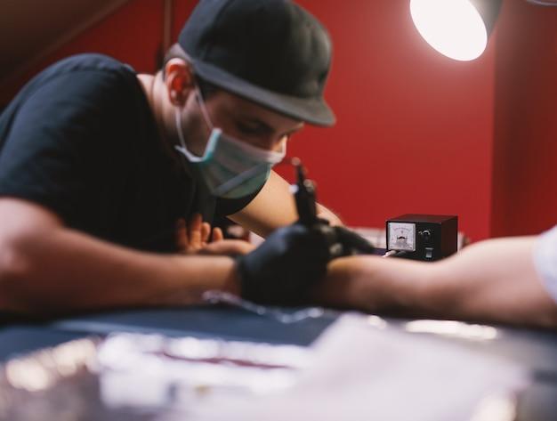 O jovem tatuador está pintando os braços dos clientes com cuidado