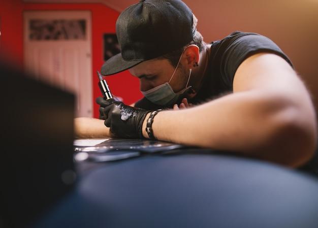O jovem tatuador focado está pintando os braços dos clientes com cuidado em sua loja.