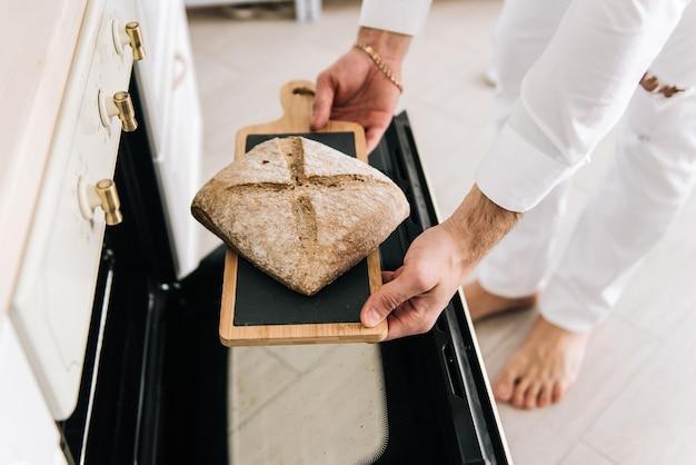 O jovem tira pão quente do forno