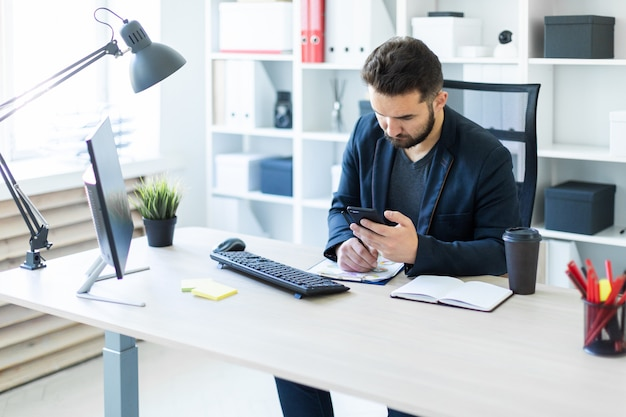 O jovem trabalha no escritório em uma mesa de computador com documentos, diagramas e telefone.