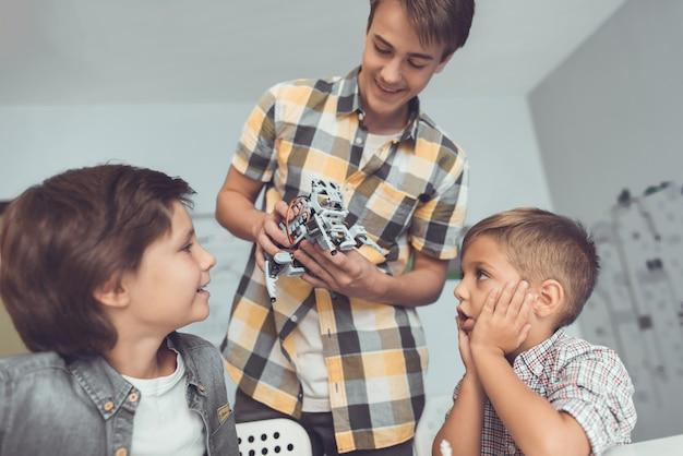 O jovem trouxe dois meninos um robô cinza.