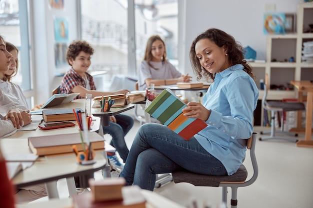 O jovem tutor está ensinando a ler seu aluno. crianças do ensino fundamental sentadas em mesas e lendo livros em sala de aula.