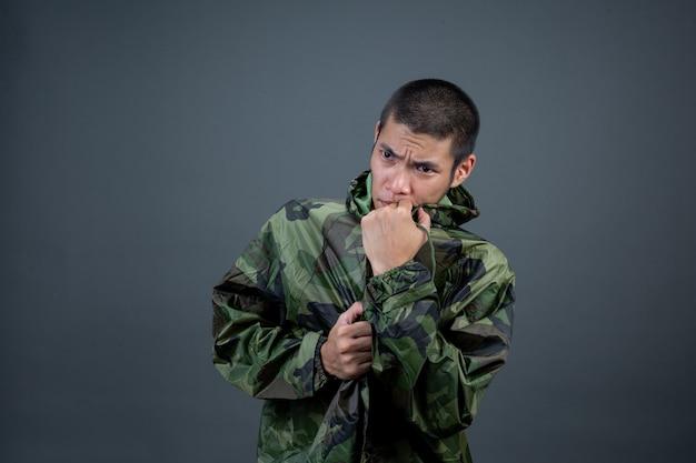 O jovem usa uma capa de chuva de camuflagem e mostra diferentes gestos.