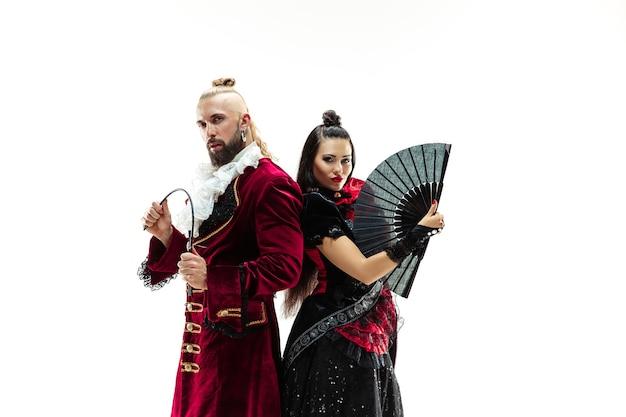 O jovem vestindo um traje tradicional medieval de marquês posando no estúdio com uma mulher como marquesa