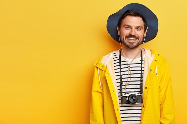 O jovem viajante alegre e ativo sorri amplamente, aproveita o tempo livre para o passatempo favorito, tira fotos com a câmera retro, vestido com capa de chuva casual e chapéu, gosta de expedição ou exploração.