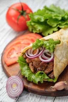 O kebab de doner está encontrando-se na placa de estaca. shawarma com carne, cebola, salada encontra-se em uma mesa de madeira velha escura.