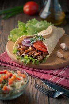 O kebab de doner está encontrando-se na placa de estaca. shawarma com carne de frango, cebola, salada encontra-se em uma mesa de madeira velha escura.