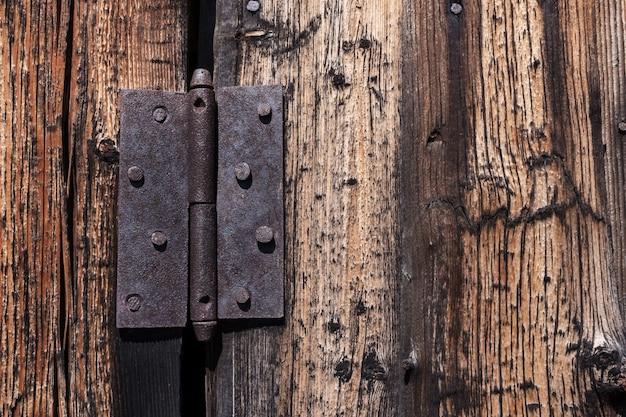 O laço oxidado do metal do close-up pregou à porta de madeira velha.