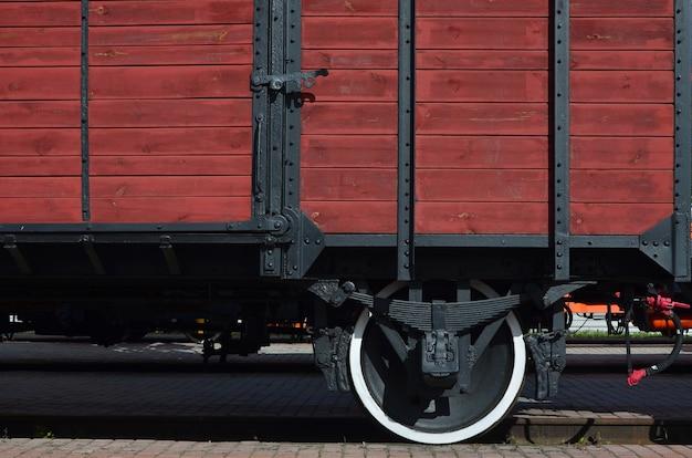 O lado do velho vagão de carga marrom de madeira com a roda dos tempos da união soviética