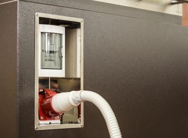 O lado externo da caixa de metal é um relé elétrico com dois interruptores de pacote em caixa de plástico e tomada para cabo de alimentação