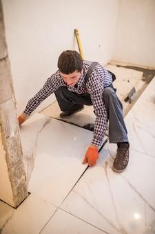 O ladrilhador do trabalhador da construção civil é adesivo para piso de ladrilho cerâmico. colocação de telhas cerâmicas.