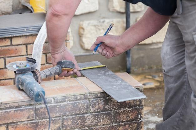 O ladrilhador mede e coloca marcas para cortar e colocar um ladrilho